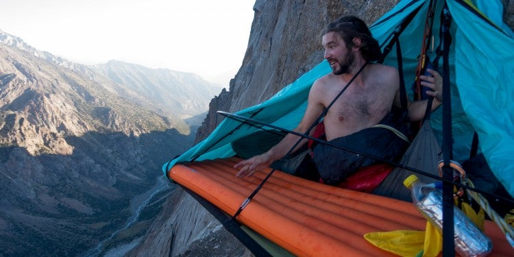 Climber waking up in bivouac on the side of a big wall.