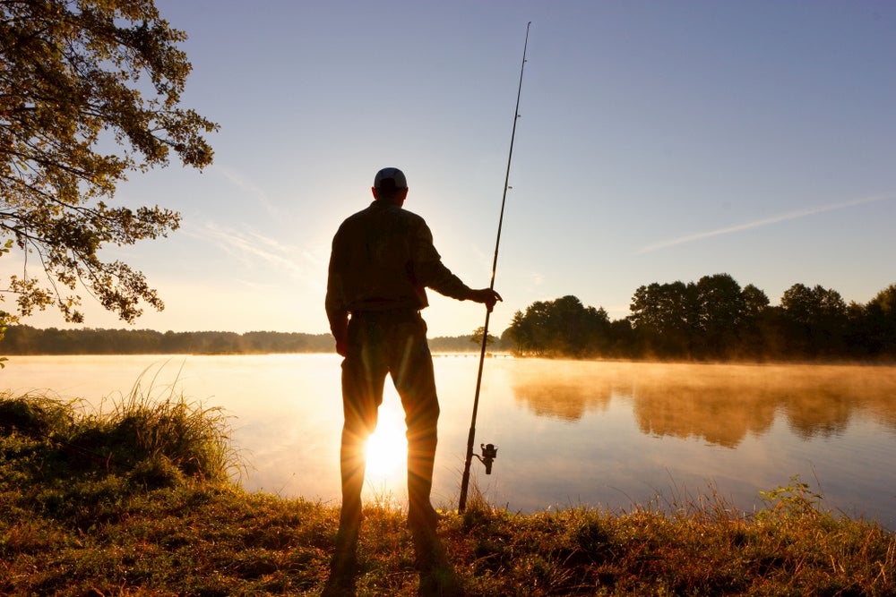 Silhouette of man fishing next to a lake
