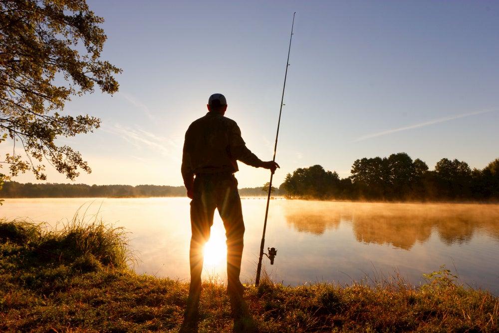 Silhouette of man fishing next to a lake