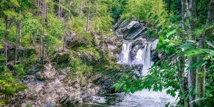 a fast flowing waterfall in vermont surrounded by rocky hills