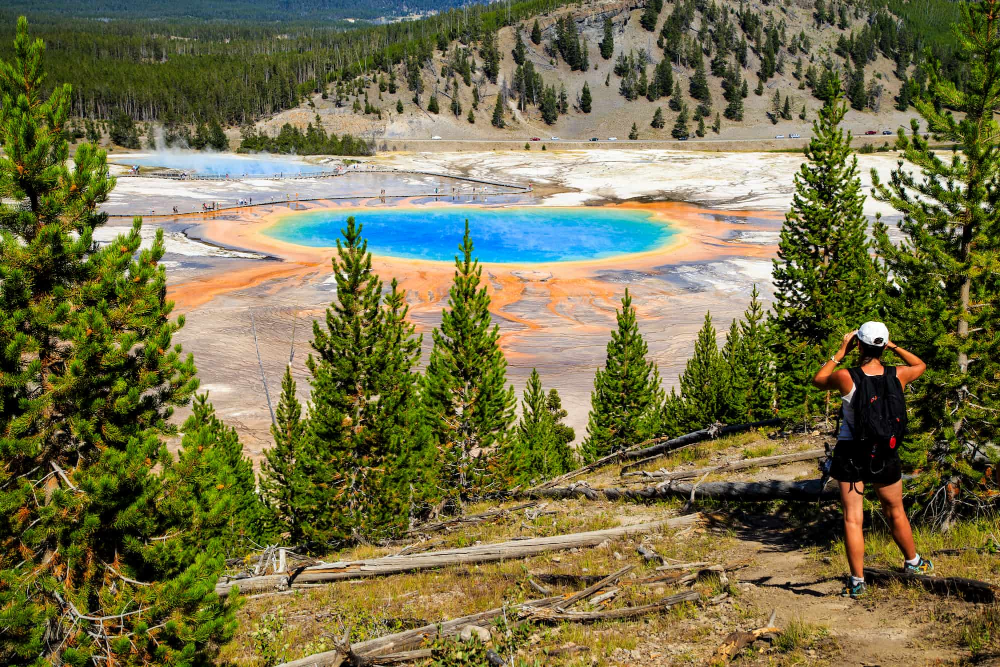 a woman looks onto a hot spring in yellowstone national park
