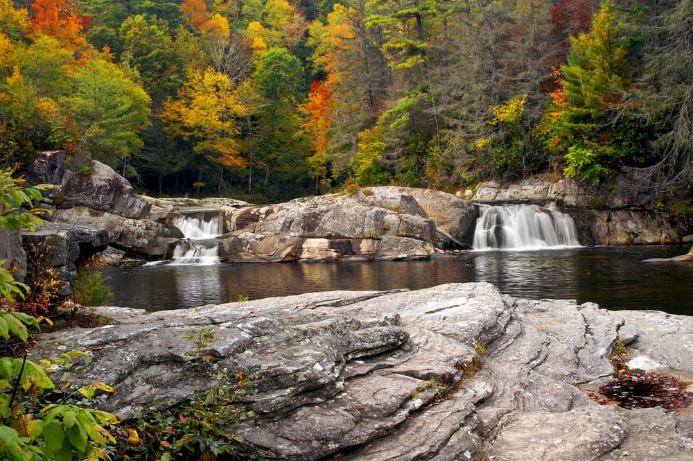 fall foliage over 2 small waterfalls with pool and rocks in foreground
