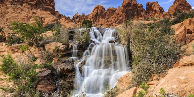 a waterfall careens over red rocks in the desert of utah