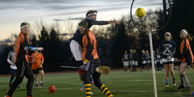 students wearing sports uniforms while playing real life quidditch
