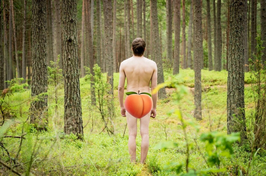a man stands naked in the woods with a peach emoji over his rear end