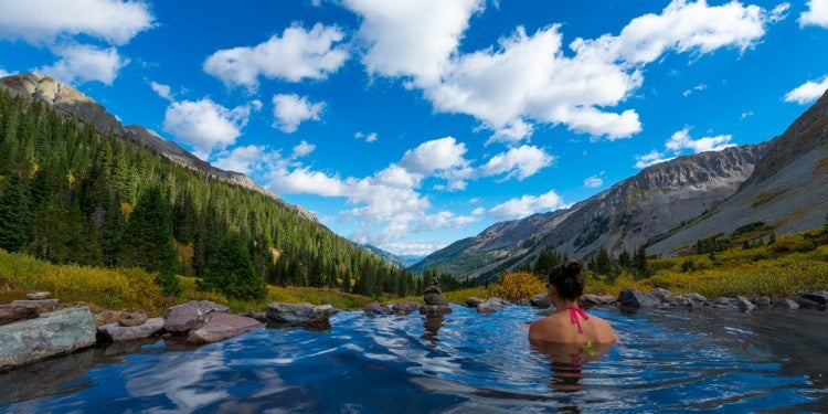 people bathing in conundrum hot springs in colorado