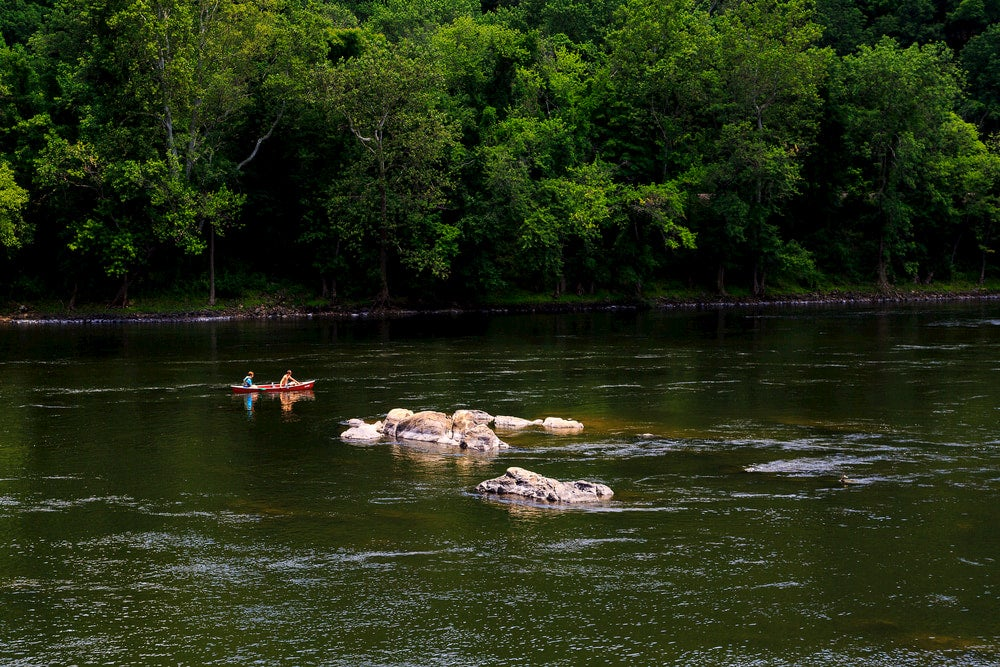 Two people paddling a canoe in the Delaware Water Gap.
