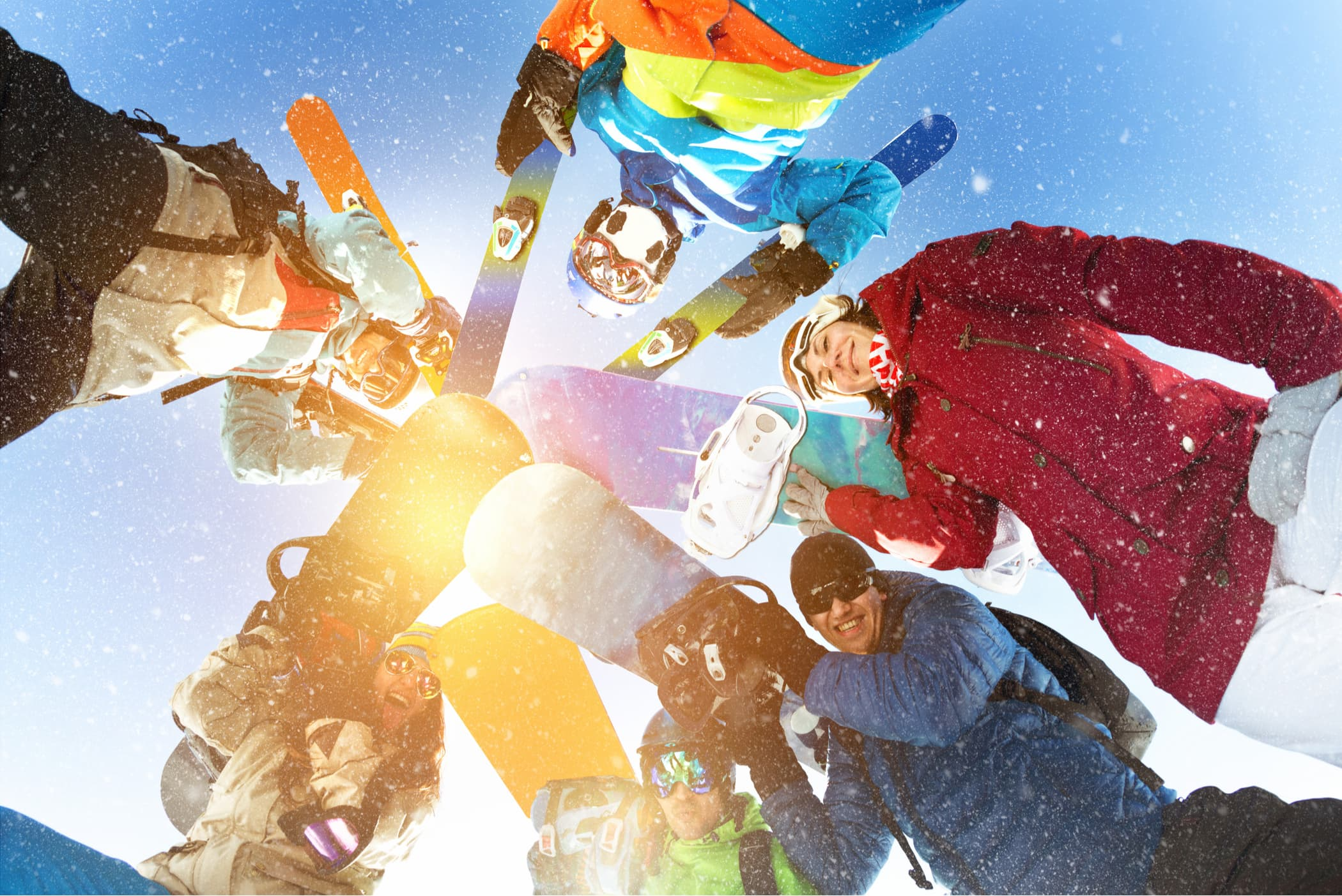 group of skiiers and snowboarders looking down on camera in a jovial circle