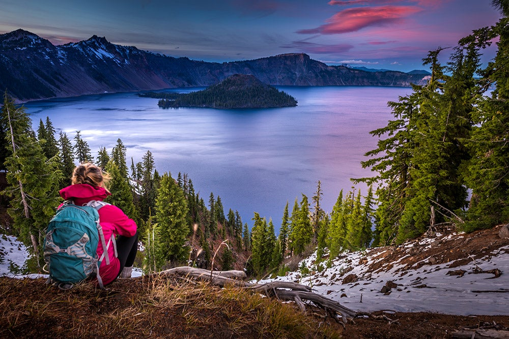 a woman on a trail overlooking crater lake national park