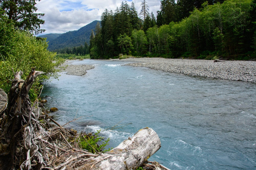 Blue rushing river with trees and mountains in background