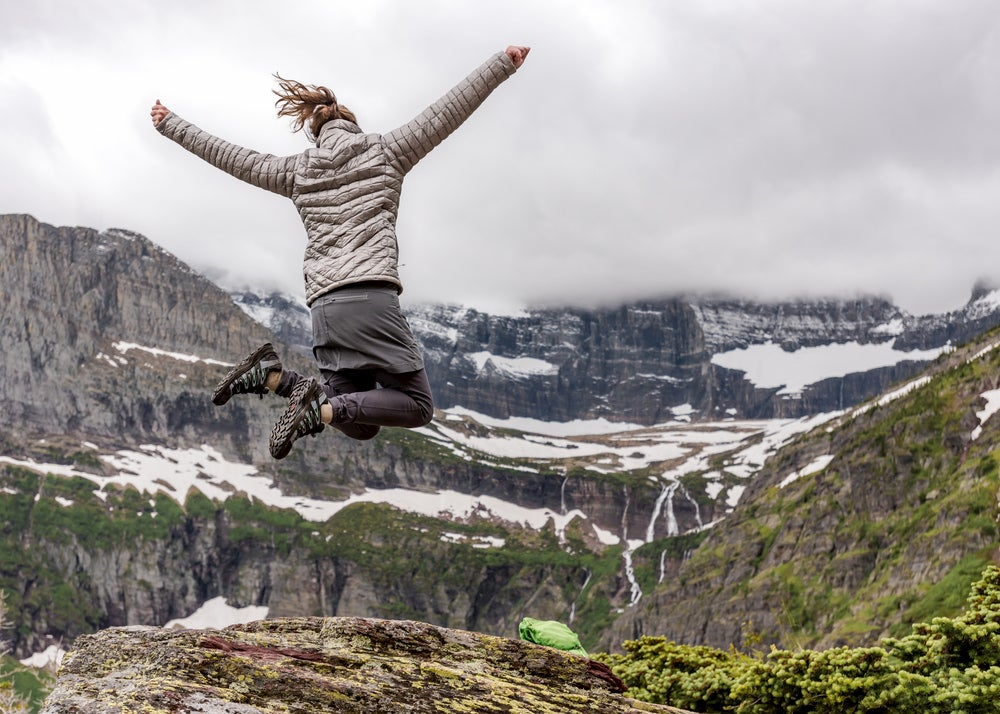 Woman in winter hiking gear jumps mid-air in front of snowy mountain range