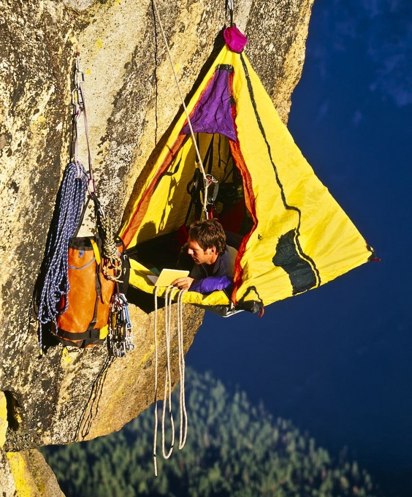 Rock climber bivouacked in his vertical camping portaledge on an overhanging cliff.
