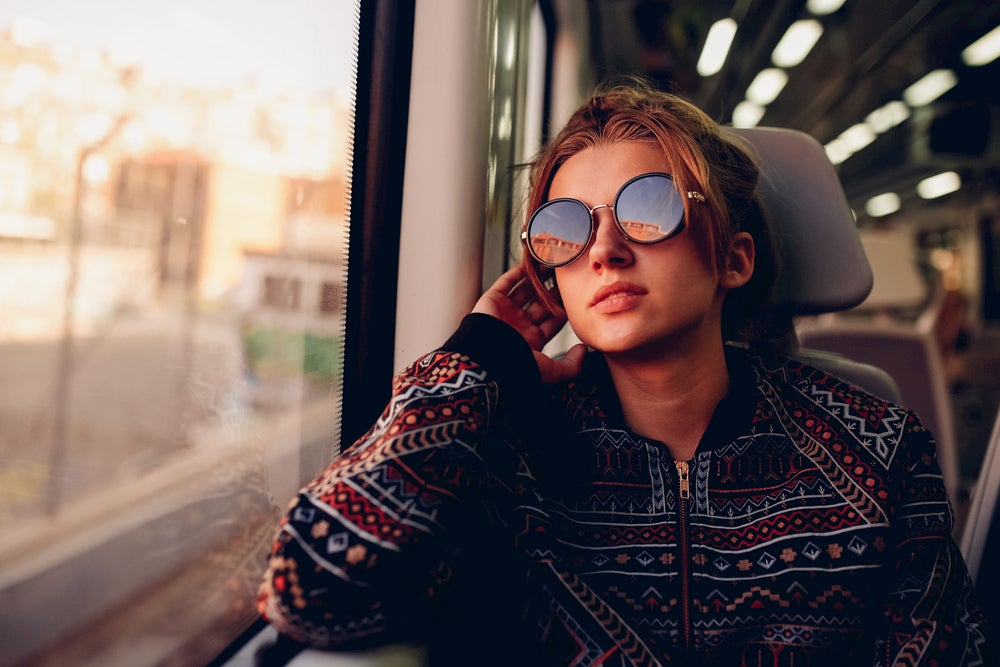 Woman wearing large, round sunglasses looks out window of train car while on the phone