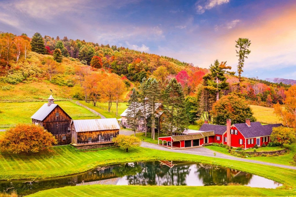 Panoramic view of red barn and old house with colorful trees in background