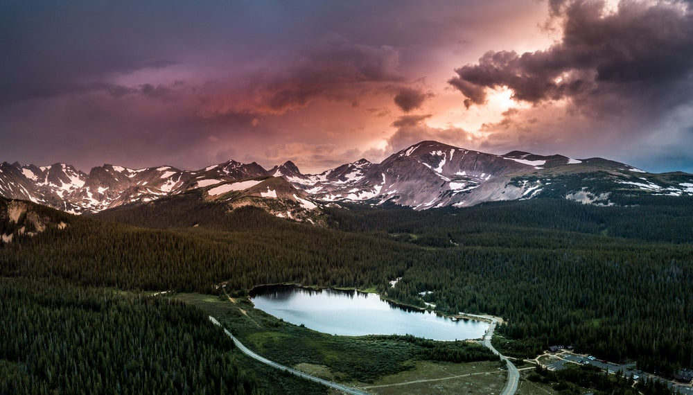 Aerial view of Indian Peaks Wilderness lake and snow capped mountains at sunset.