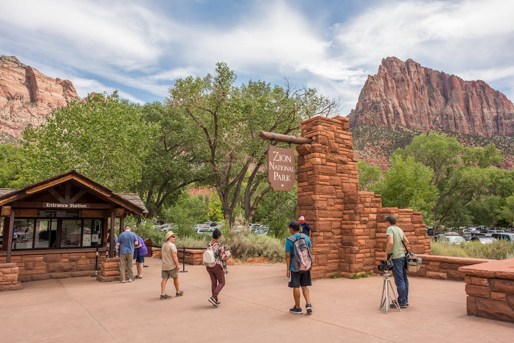 a group of visitors walk toward the entrance of Zion National Park beneath large red rock formations