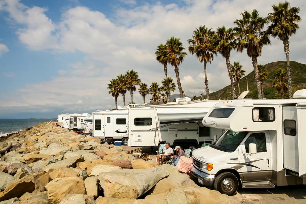 rvs parked along rock wall and beach with palm trees