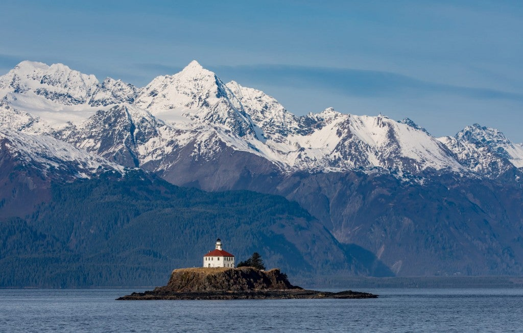 Panoramic view of snow-capped mountains and island with lighthouse on island