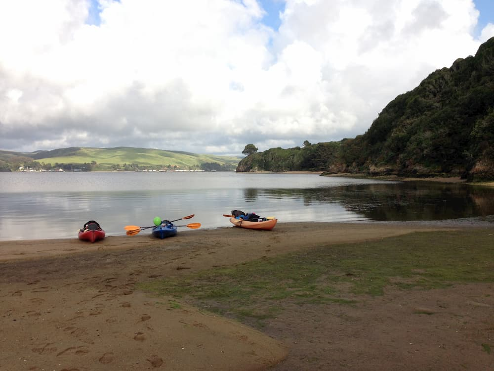 3 kayaks sit on sandy shore with lake and rolling hills in the background