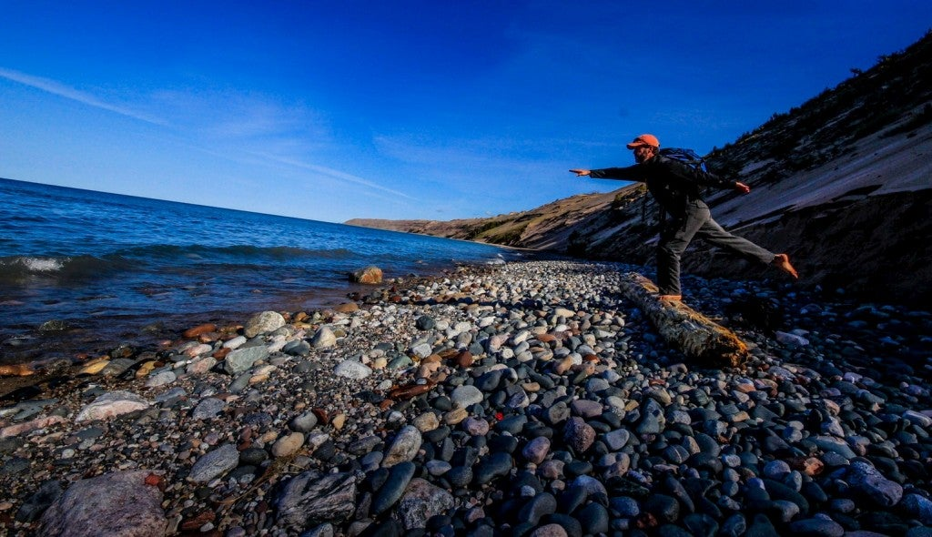 Man posing on a log on a stone beach.