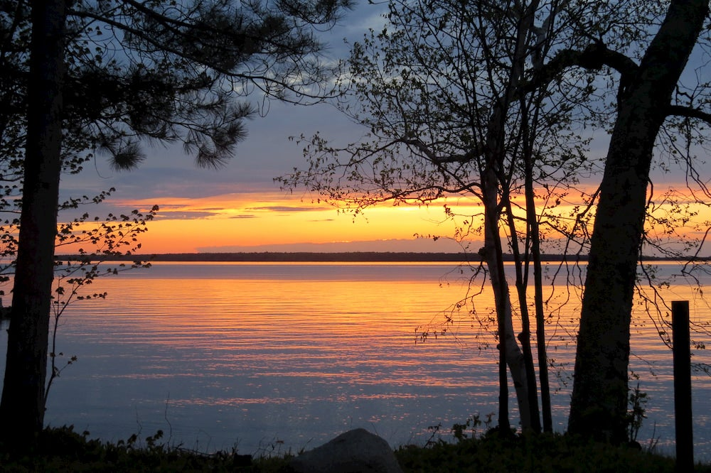 Orange sunset reflecting onto calm waters in the apostle islands