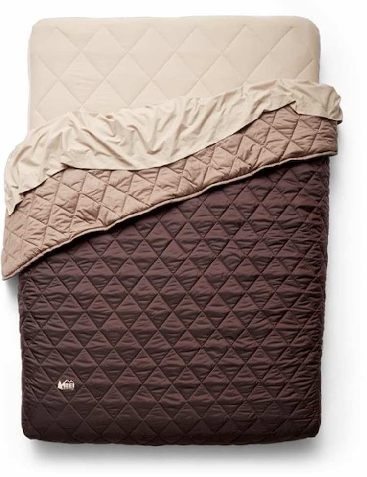 a camping air mattress set up with a quilt and sheet
