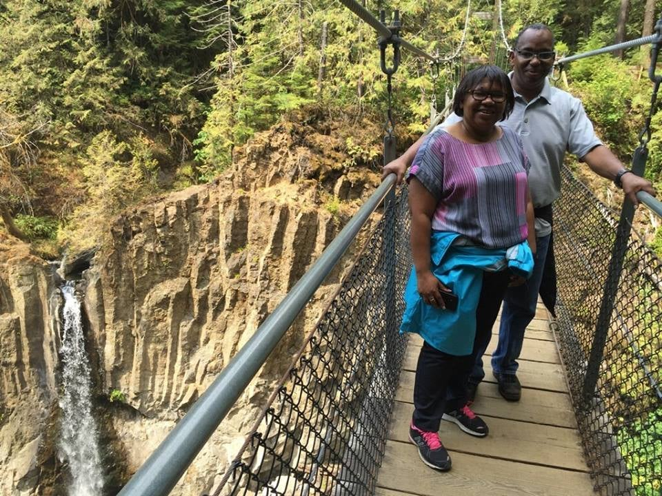 Myrna and Sheldon standing on a bridge over a gorge with a waterfall in the background