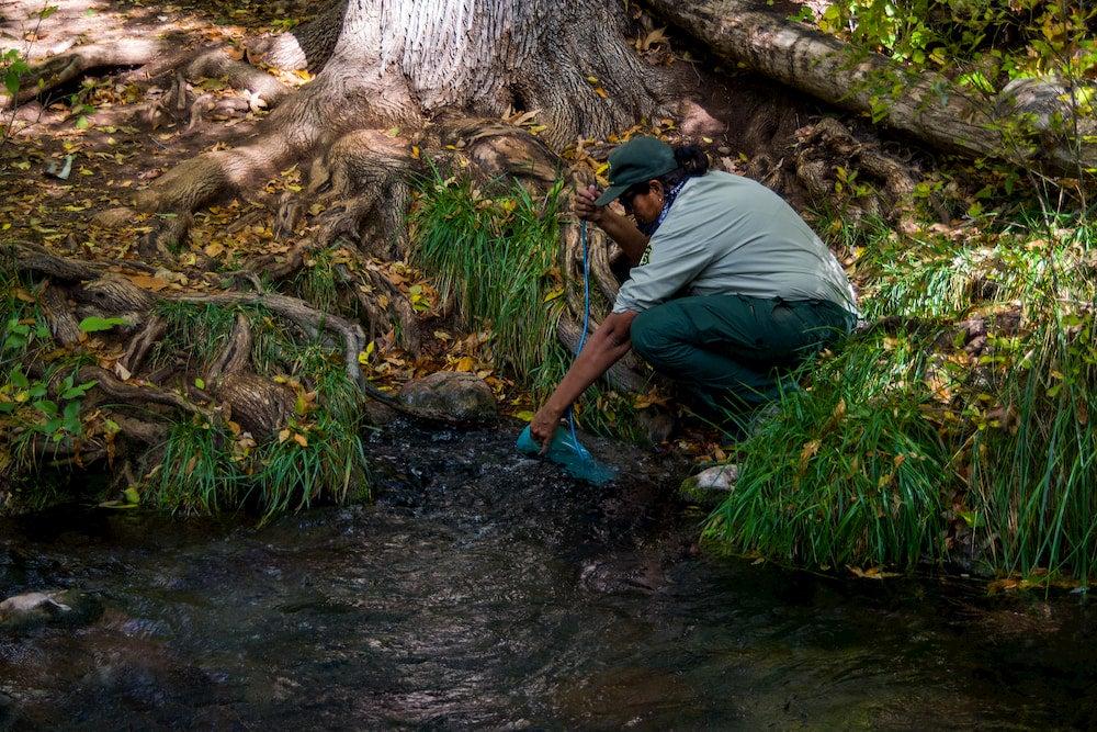 a park ranger fills her water bladder in a river
