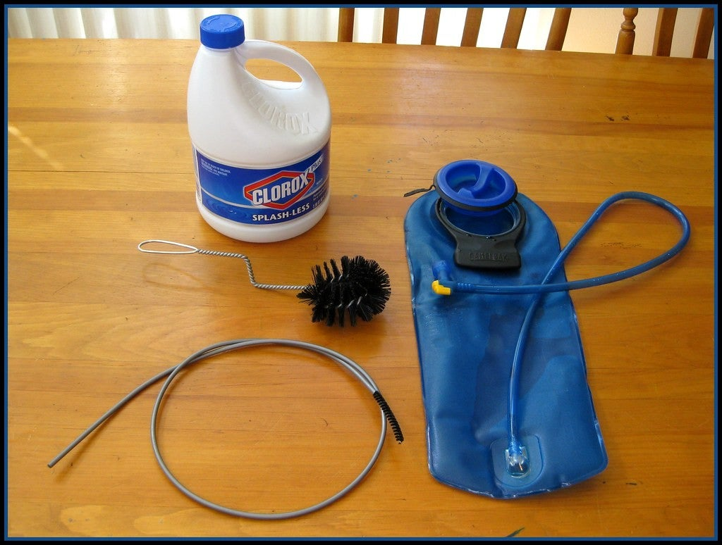 a bottle of bleach, a cleaning brush and pipe and a water bladder on a table