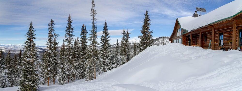 Wooden hut half buried under an alpine snowdrift