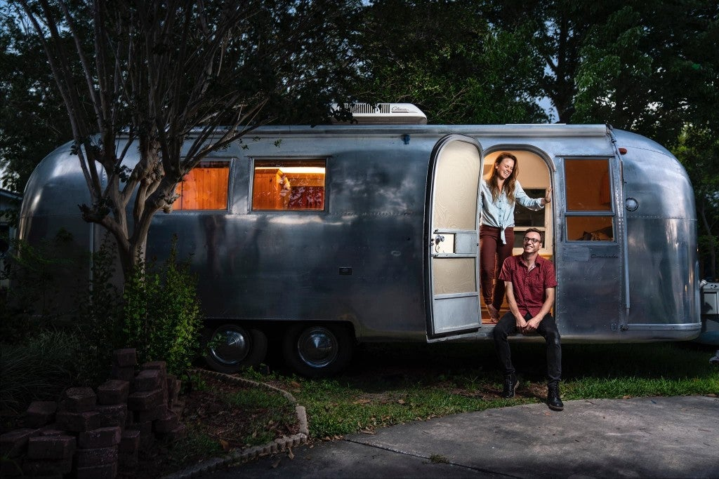 a woman next to a man at the entrance to an airstream trailer parked at a campground