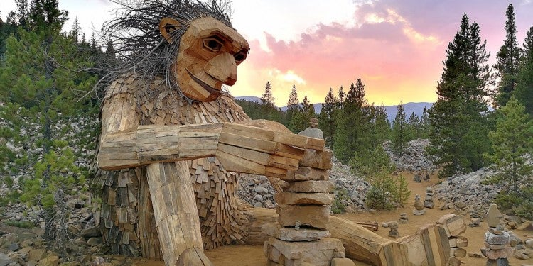 Isak Heartstone the wooden troll sculpture sitting on the ground building a rock carin