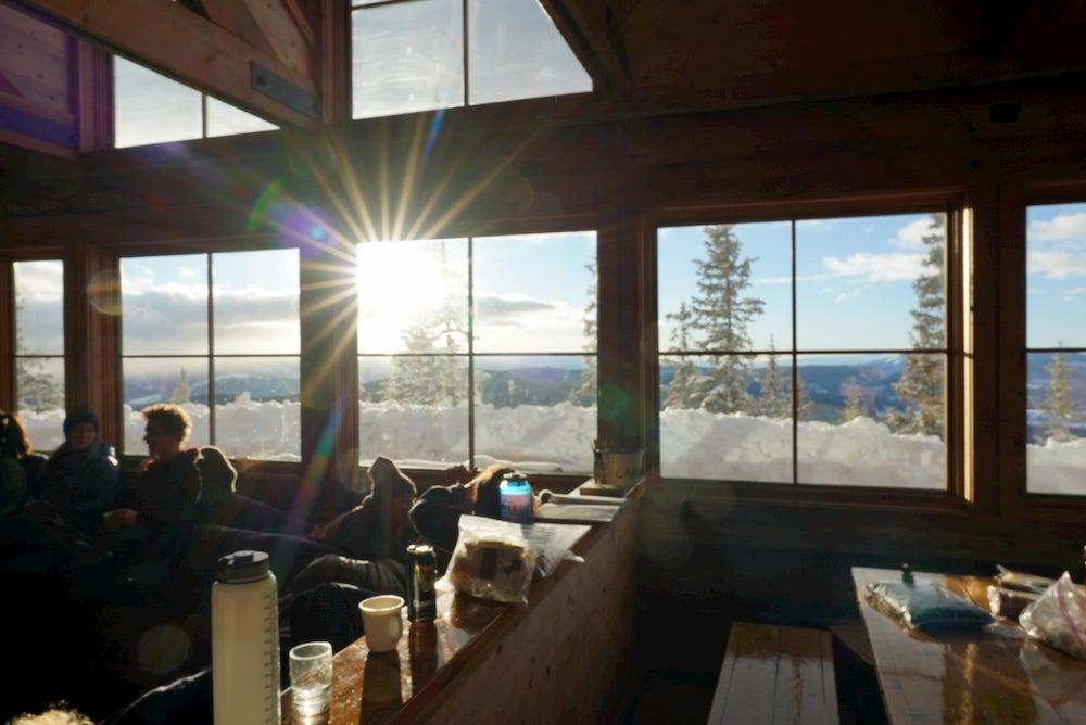 Sun shining through the a wooden hut into a cozy living room.