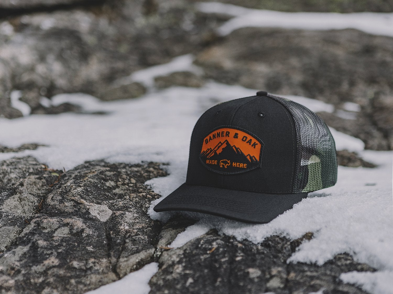 a trucker hat rests on a snowy field