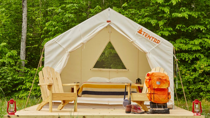 a tentrr glamping tent in maine set up with chairs, a bed and a tent on wood