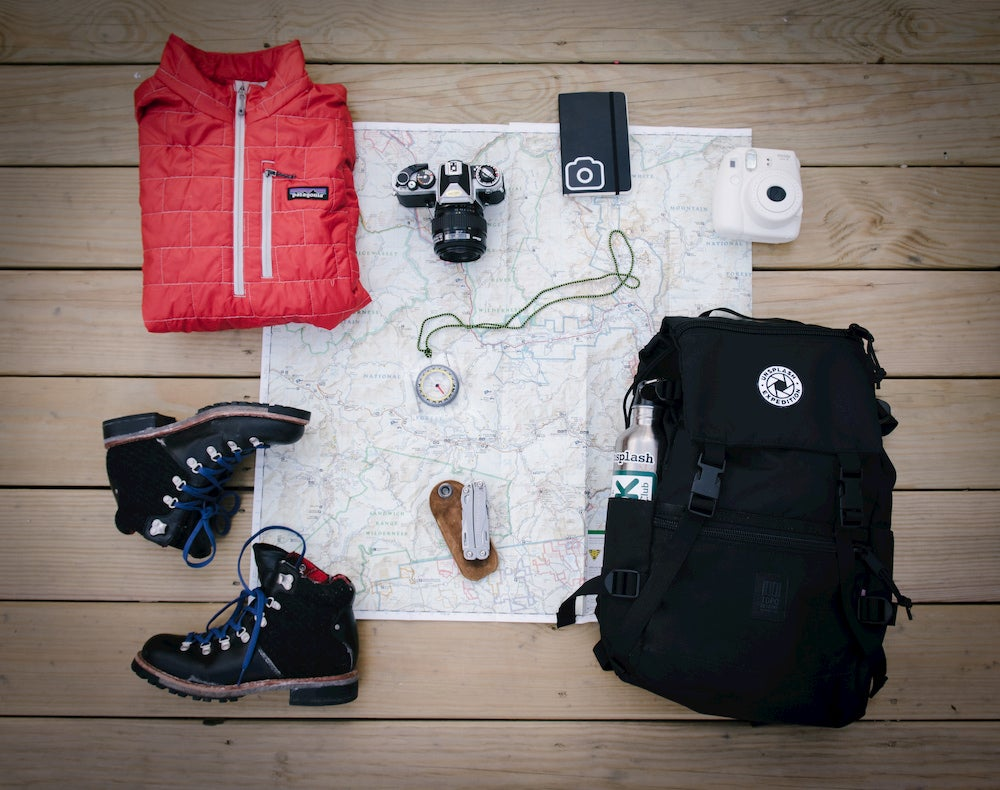 Day hiking gear laying flat atop map on wooden deck.