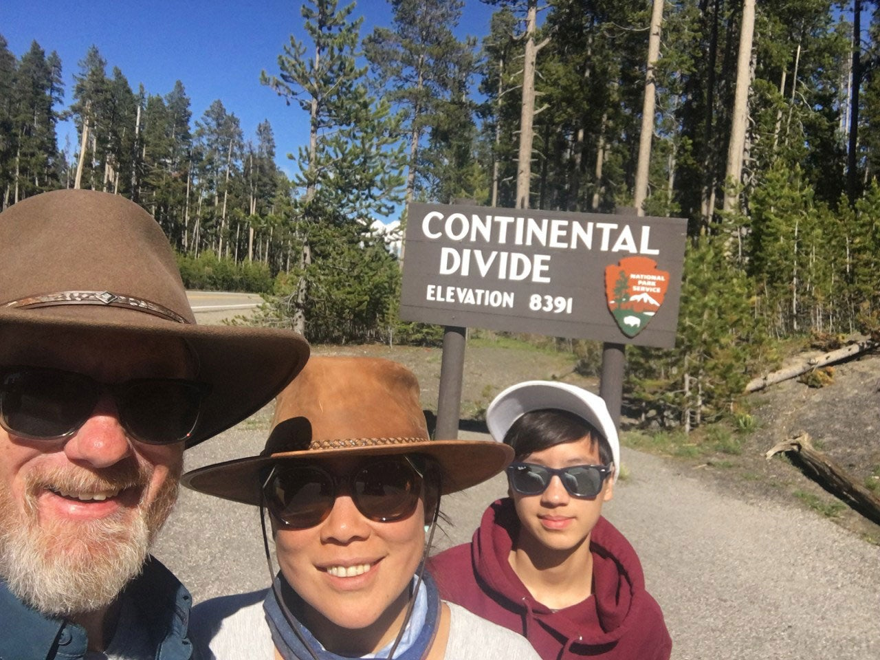 three people in front of a NPS sign for the continental divide