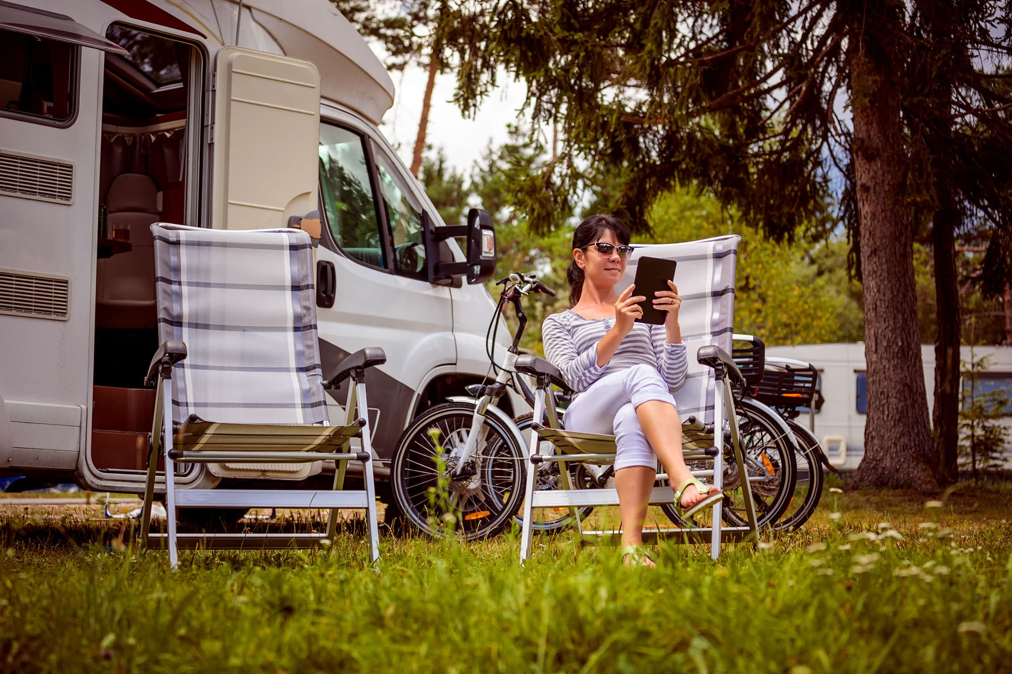 a woman holding a phone in a camping chair near an RV at a campground