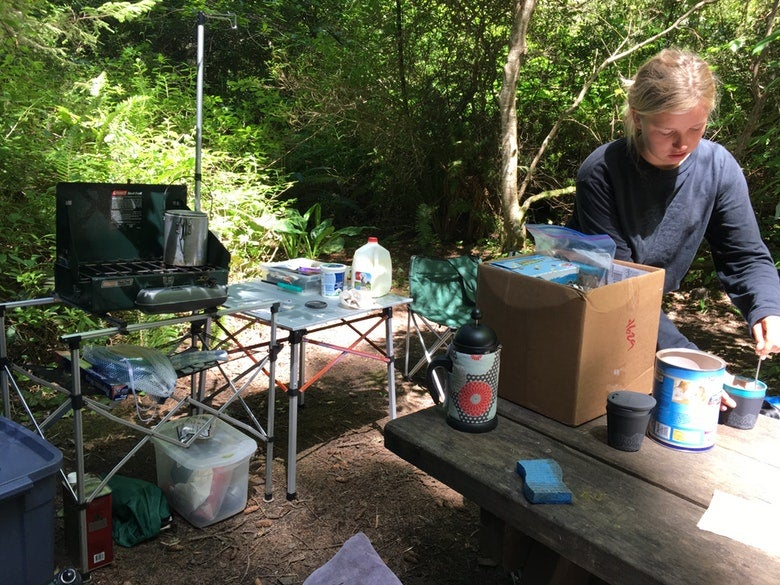 a woman at a campsite cooking in a makeshift camping kitchen with food and utensils surrounding