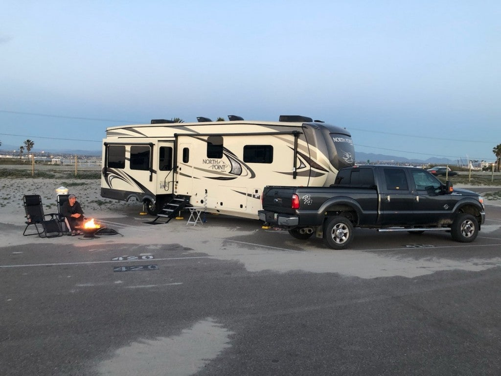 truck and large RV parked on a sandy RV parking spot with a fire going beside the site