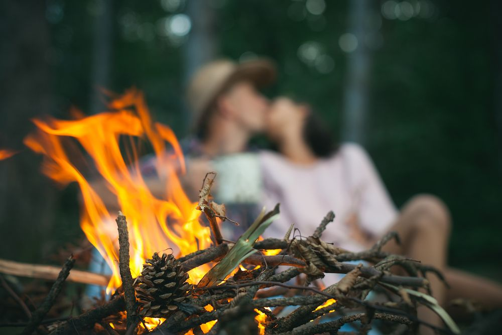 camera focuses on twigs burning in campfire as couple kisses in the background out of focus