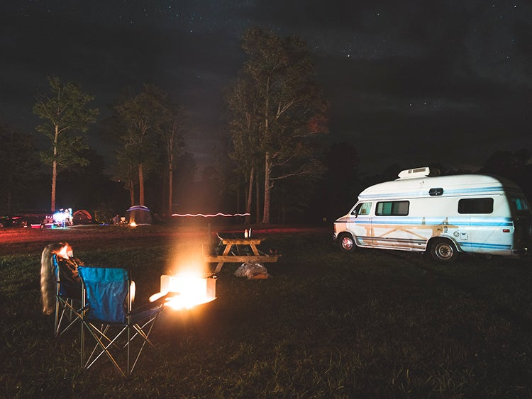 two chairs in front of a campfire near a parked RV at the cherry springs state park campground
