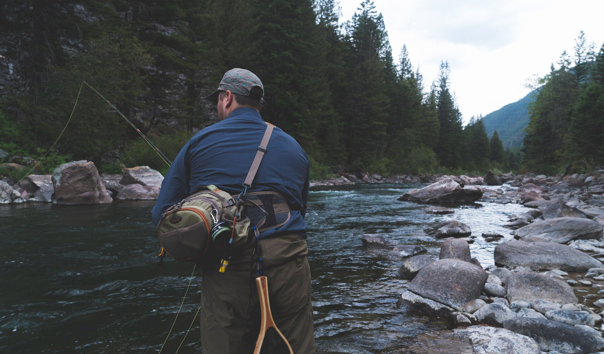 Fly fisherman casting in an alpine river.