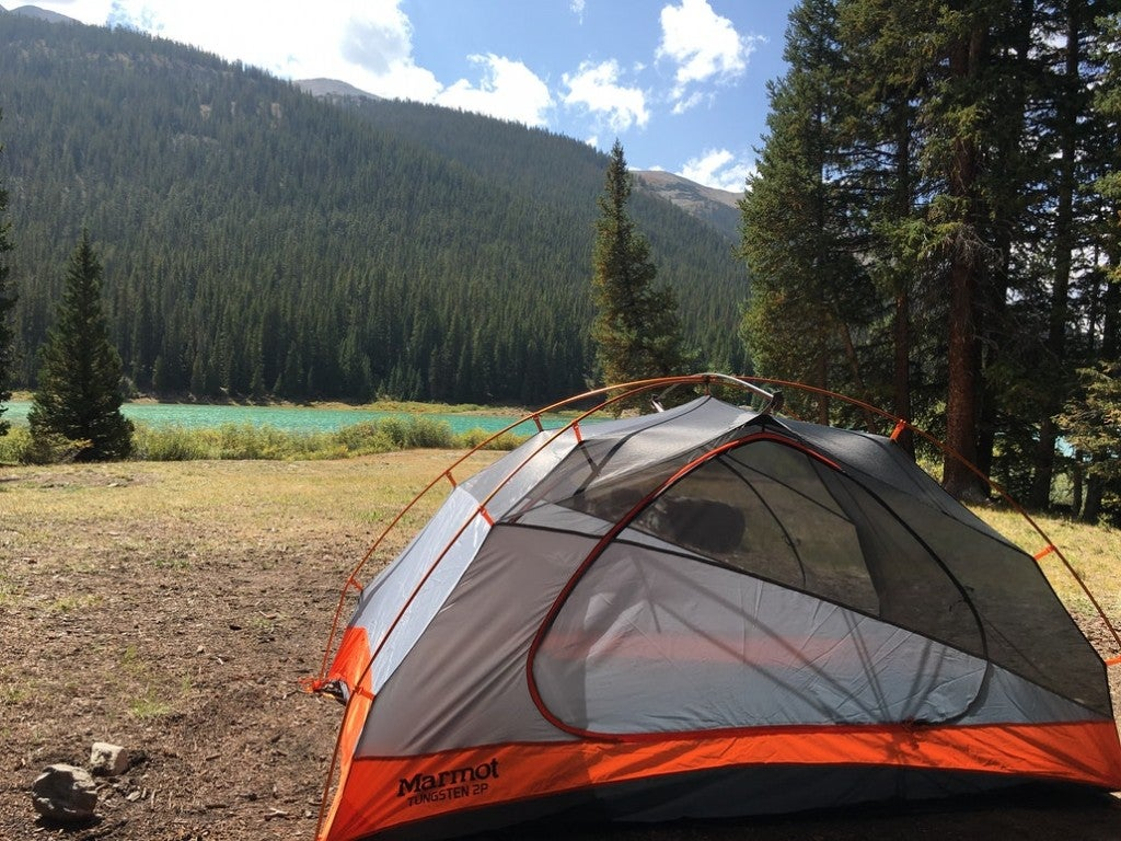 a marmot tent set up on a field close to a river near mountains in colorado