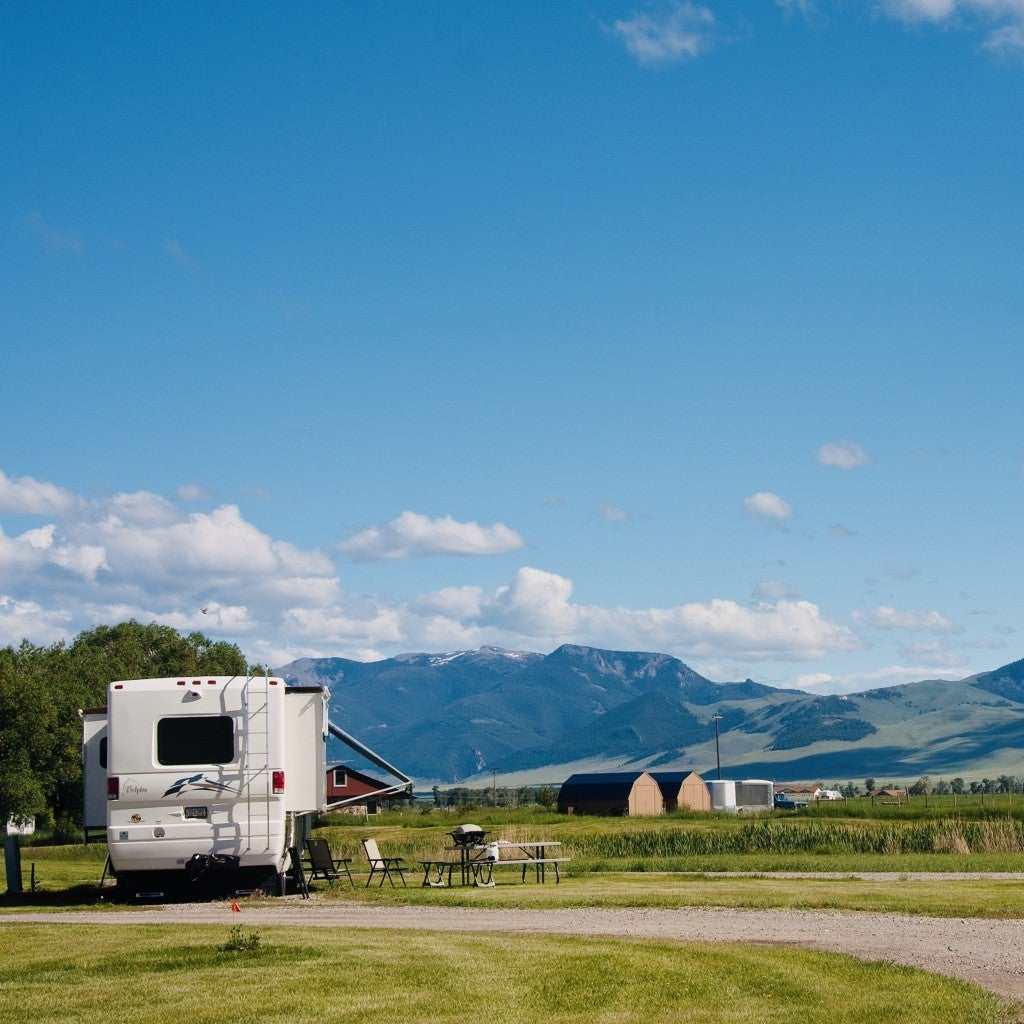 an RV camper set up at a campground looking at far away mountains in montana