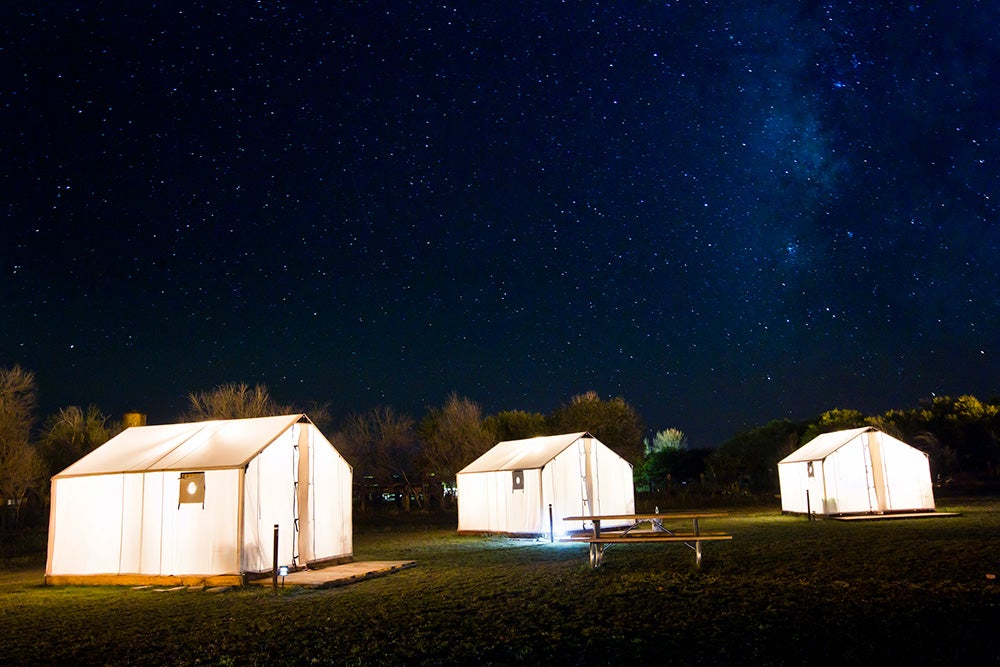 three canvas cabins for glamping in texas lit up at night