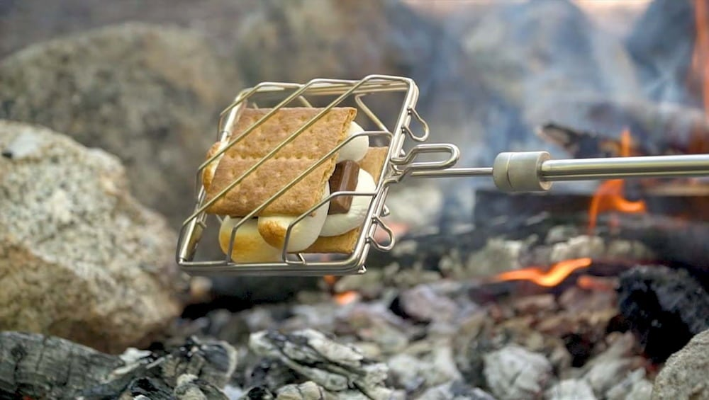Smores being cooked over fire in a grubstick cage