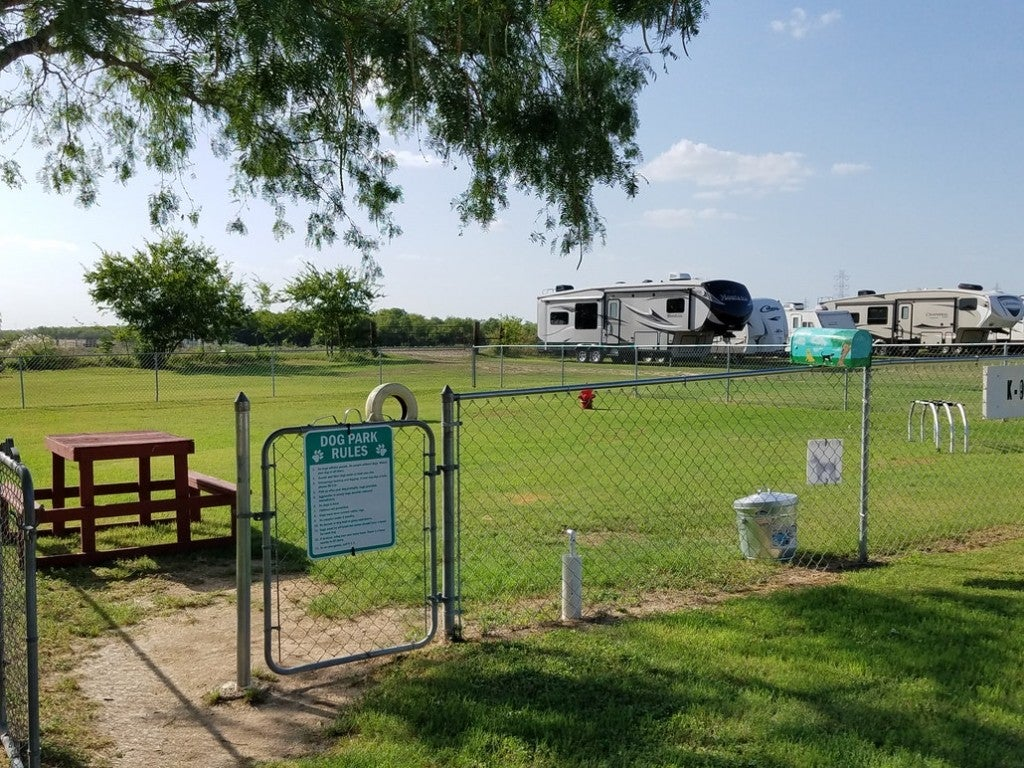 a fenced dog park at a campground in texas with RVs in the distance