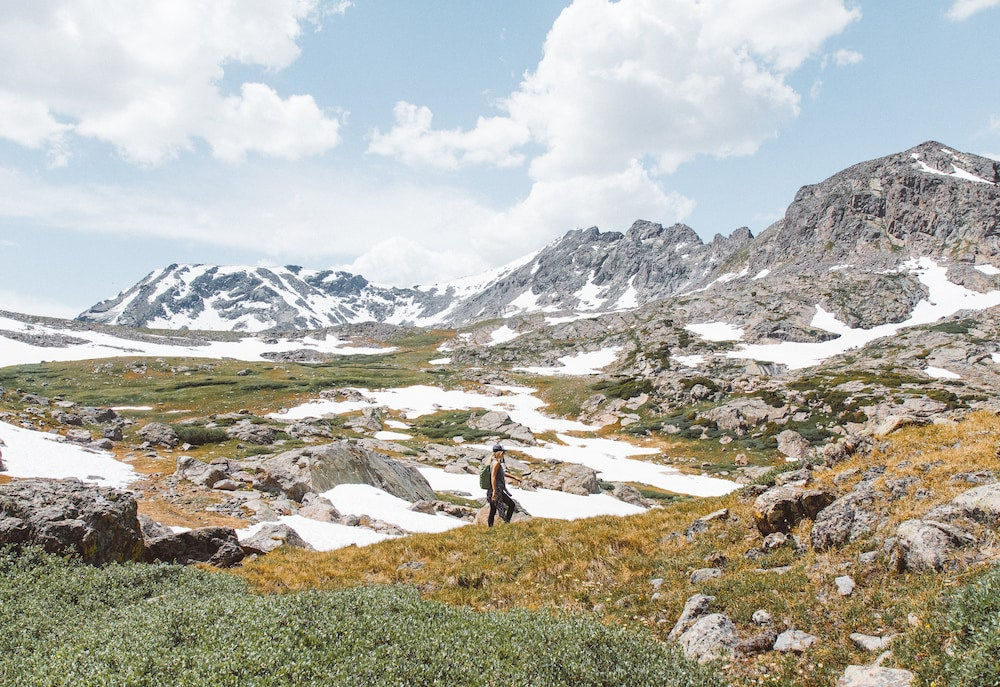 Woman backpacking in Colorado in summer snowmelt.