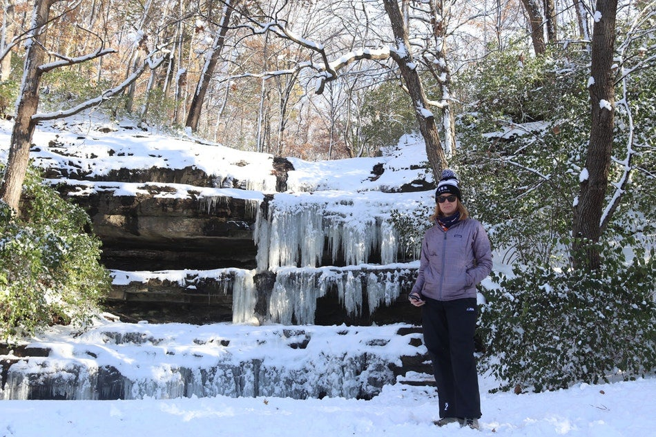 woman standing in front of frozen waterfall in the shawnee national forest